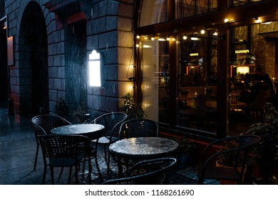 summer cafe tables on the street in heavy rain