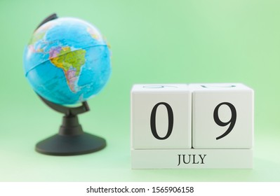 Summer calendar for July 9 from wooden cubes with numbers on a blurry green background, near the globe.