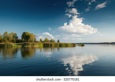 Summer calm lake and sky with fluffy clouds