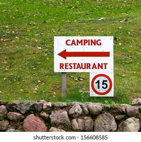 Summer camp sign post background, Tent camping and restaurant sign in natural nature blur background,Camp sign. Dirty camp sign.Directional sign pointing towards CAMP and Restaurant area. Speed limit