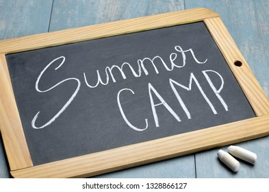 SUMMER CAMP written on chalkboard on blue wooden background