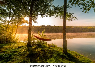 Summer camping on the lake. Empty hammock  between two trees with the view of a foggy mountain lake in sunrise light. Outdoors and adventure concept.