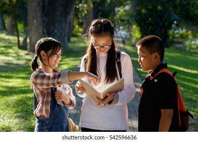 Summer Campus Concept. groupof Asian student reading a book in park.