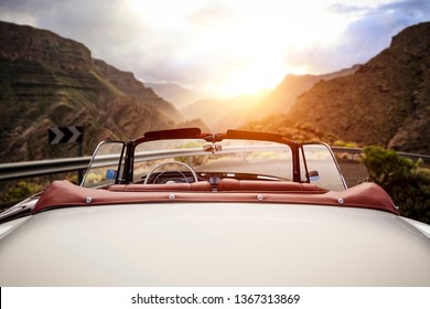 Summer car on road and sunset time in mountains. Free space for your decoration.