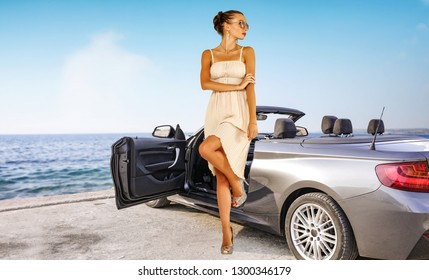 Summer car with slim young woman and silver cab on coast. Sea landscape with blue sky.
