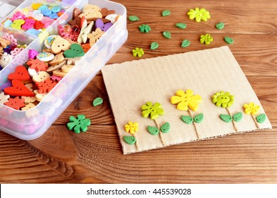 Summer card with yellow and green flowers. Postcard made of cardboard, buttons and cord. A box of colorful buttons on a brown wooden background. Simple kids crafts