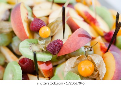 Summer catering composition of fruits: peach, raspberry, physalis and kiwi on a white plate