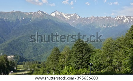 Summer in the Caucasian mountains, green trees and snow-capped peaks, ski resort Rosa Khutor, Russia