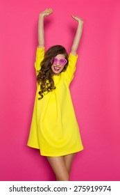 Summer Celebration. Beautiful girl in yellow mini dress and pink heart shaped sunglasses posing with arms raised. Three quarter length studio shot on pink background.