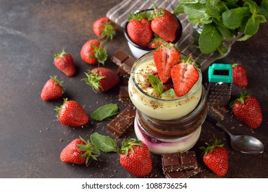 Summer cheesecakes in jars on a brown background
