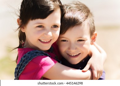 summer, childhood, family, friendship and people concept - two happy kids hugging outdoors