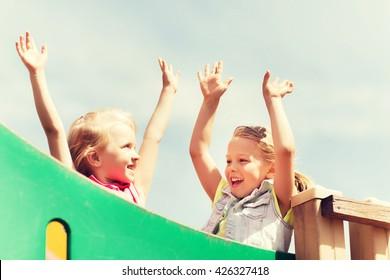 summer, childhood, leisure, friendship and people concept - happy little girls waving hands on children playground climbing frame
