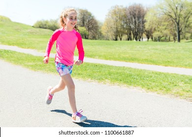 summer, childhood, leisure and people concept happy little girl running