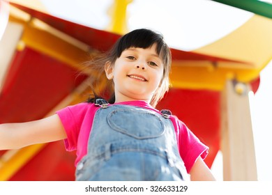 summer, childhood, leisure and people concept - happy little girl on playground climbing frame