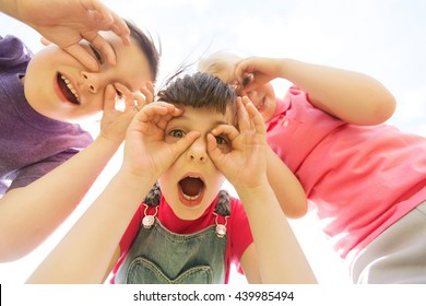 summer, childhood, leisure and people concept - group of happy kids having fun and making faces outdoors