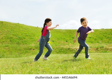 summer, childhood, leisure and people concept - happy little boy and girl playing tag game and running outdoors on green field