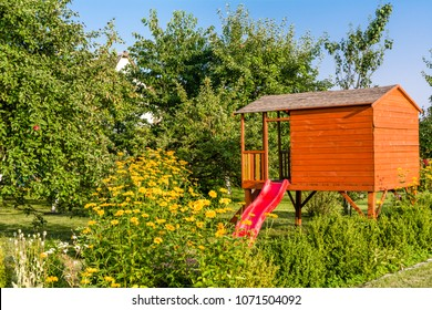 Summer children house in the garden, cottage playhouse for kids