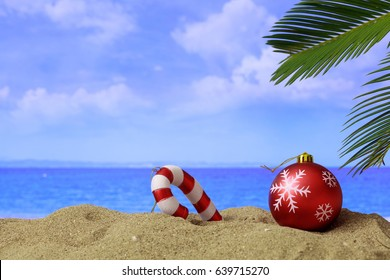 Summer Christmas holidays. Christmas ball and ornament on a sandy beach, copy space