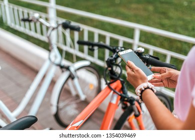 In summer city background parking bicycles girl chooses route application, Internet online map phone. Route bike path. Bicycle parking city. Rental and blocking, protection application Internet.