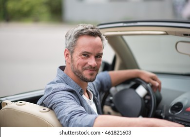 Summer in the city. Looking at camera an handsome man driving her convertible car