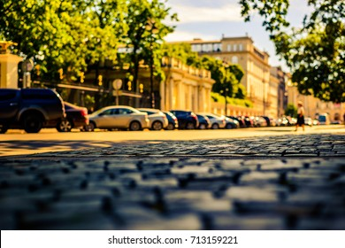 Summer in the city, the pedestrian is walking down the street with a paved stone near the park. Close up view from the level of paving stones, image in the yellow-blue toning