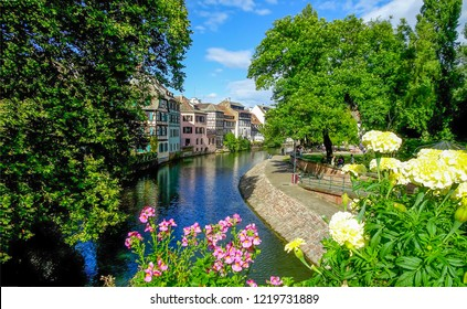 Summer city river flowers view. River city flowers view. European river town flowers scene