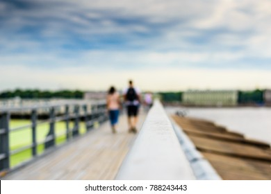 Summer in the city, a walking terrace with panoramic views of the city and walking people. Close up view from the handrail on the sidewalk level