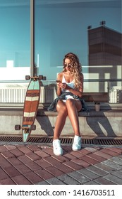 Summer city, woman writes message phone, online internet application, correspondence social networks. Reading news tapes smartphone. Skate longboard, long hair cup coffee tea. Free space for text