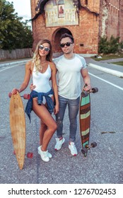 In the summer in the city a young couple holds skateboards and longboards. Resting in the city, girl in white swimsuit bodysuit, guy in a T-shirt and jeans. The concept of youth recreation.