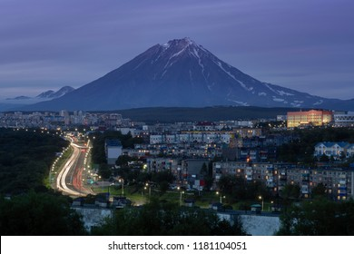 Summer cityscape of Kamchatka Peninsula: night view of urban development of Petropavlovsk-Kamchatsky City, driving automobiles on city asphalt road on background of volcano. Eurasia, Russian Far East.