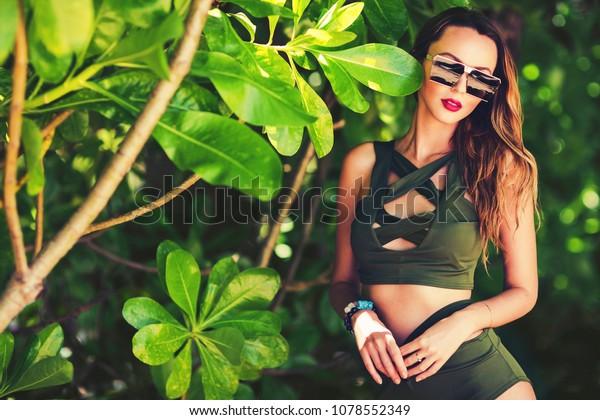 Summer close up fashion portrait of stunning women with slim sexy body. Enjoying life in paradise. Wearing stylish high waist bikini and sunglasses. Mangrove trees background. Tropical island beach