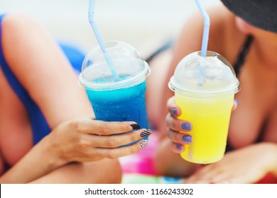 Summer close up image of two glasses of fresh colored lemonade in hands of two pretty girls on the beach of tropical island. Tasty cold slush drinks. Bright colors. Holiday tropical concept. Sunny day