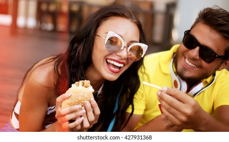 Summer Close up lifestyle image of couple in love hugging having fun,laughing and smiling together.Handsome boyfriend joke of her girlfriend and feed her.french fries,fashion couple in sunglasses.