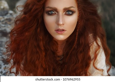 Summer close up outdoors portrait of beautiful scandinavian warrior viking ginger woman in a traditional historical clothes and landscape view on the background.