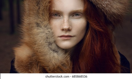 Summer close up outdoors portrait of beautiful scandinavian warrior viking ginger woman in a traditional clothes with fur collar and forest view on the background.