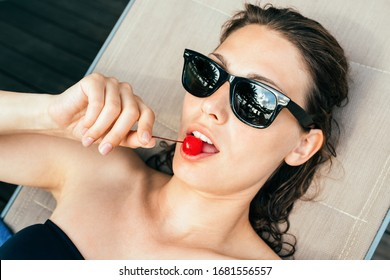 Summer closeup of sexy young beautiful woman eating red cocktail cherry outdoor on the beach