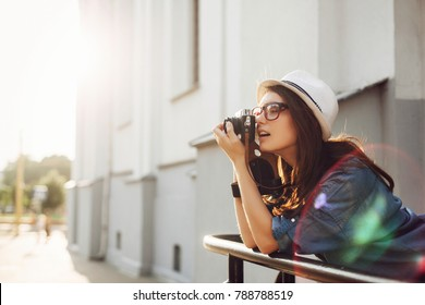 Summer closeup street portrait of young smiling beautiful and happy woman photographer posing with camera, wearing a hat