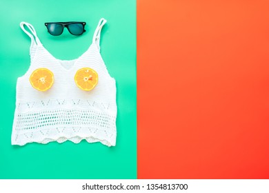 summer clothes concept from Women's Clothing, Camisole, Sunglasses and Half cut orange, flat lay on red and green background pastel color for advertising sale products.