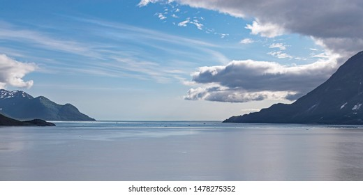 summer clouds gather over the mouth of disenchantment bay in yakutat bay in alaska with the tip of haenke island on the left