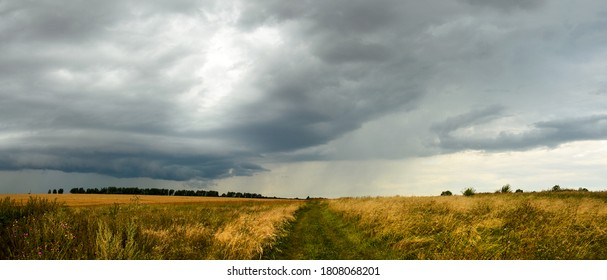 Summer cloudy panoramic landscape with rural road passing through meadows and fields.Ominous clouds in overcast sky over the ripe wheat agricultural fields.Heavy rain and thunderstorm coming.