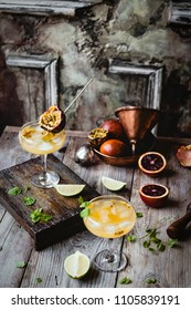 summer cocktail decorated with passionfruit half on wooden board and on wooden table with fresh limes, blood oranges and passionfruit with metal kitchen ware on backside