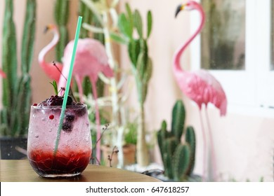 Summer Cocktail or Tropical Mocktail - A Glass of Iced Mixed Berries with raspberry, blueberry, red berry and soda on wooden table background, Selective Focus.