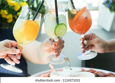 Summer cocktails. Cheers, people holding cocktails in the hands
