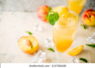 Summer cold alcohol beverage, iced peach Bellini cocktail with mint leaves, light concrete background copy space