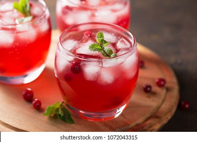 Summer cold beverage with cranberry, ice cubes, mint on the wooden cutting board. Healthy berry drink in three glasses.