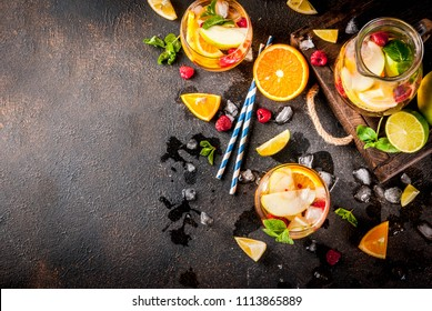 Summer cold cocktail, fruit and berry white sangria with apple, lemon, oranges and raspberry. dark background, copy space top view