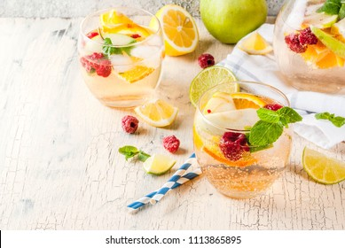 Summer cold cocktail, fruit and berry white sangria with apple, lemon, oranges and raspberry. light concrete background, copy space
