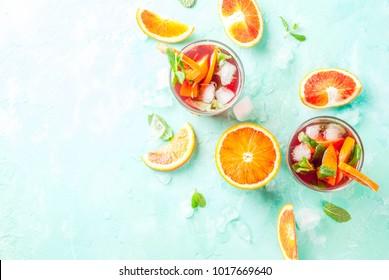 Boisson froide estivale, cocktail de menthe orange sanguine - mimosa, mojito ou sangria, arrière-plan bleu clair, vue de dessus sur l'espace pour copie