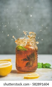 Summer cold Iced tea with fresh bergamot, mint and lemon in glass jar with splashes, grey concrete wall at background, copy space. Food in motion concept