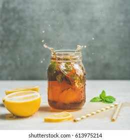Summer cold Iced tea with fresh bergamot, mint and lemon in glass jar with splashes on light table, grey concrete wall at background, copy space, square crop. Food in motion concept